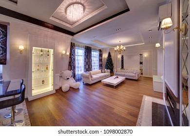 The big living room with white furniture and a dark wooden parquet