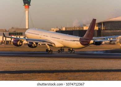 Big long haul widebody passenger airplane with four engines delivers passengers and cargo is touching down the runway at the destination airport during sunset illumination. Tail view with ATC.