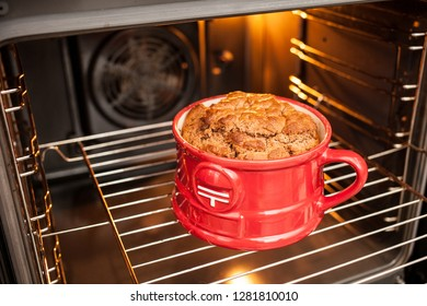 a big lush ruddy mugcake in a red mug cooked in the oven. Cooking and cupcake recipes Realism