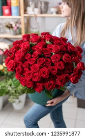 Big luxury bright bouquet in the hands of a cute girl. One hundred of garden red roses. Color passionately scarlet, Autumn mood. bouquet in a hat box
