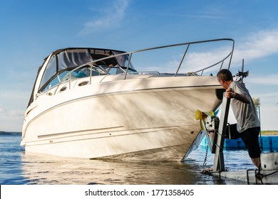 Big luxury cabin motorboat cruiser yacht launching at trailer ramp on river or lake. Mechanic worker man assist putting boat in calm water surface. Luxury rich fishing leisure recreation lifestyle