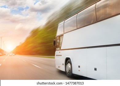 Big luxury comfortable tourist bus driving through highway on bright sunny day. Blurred motion road. Travel and coach tourism concept. Trip and journey by vehicle