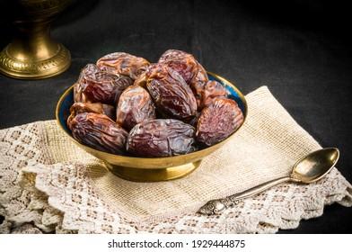 Big luxury dried date fruit in bowls on a linen napkin, kurma ramadan kareem concept.