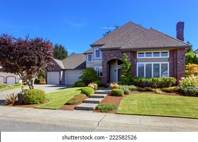 Big Luxury House With Tile Roof And Brick Wall Trim. Walkway Decorated With  Flower Pots