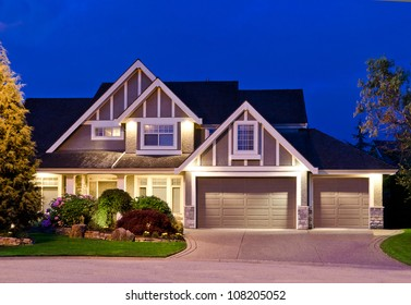 Big luxury house with triple garage doors at dusk, night in suburbs of Vancouver, Canada