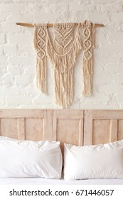 Big macrame on a white brick wall in bedroom