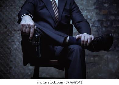Big mafia boss posing with his weapon