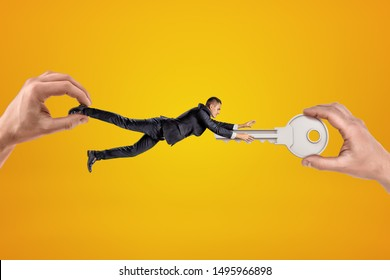 Big male hand holding tiny businessman who is reaching to another big hand holding silver metal key on yellow background. People and objects. Digital art. Private property.
