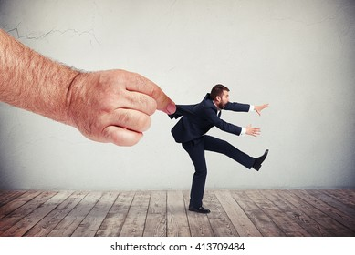 A big male's hand is pulling a man in in dark grey business suit backwards while the man is vigorously trying to resist