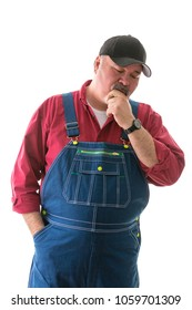 Big man in denim bib overalls and cap standing thinking looking down at the floor with his hand to his chin isolated on white