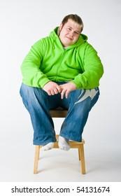 Big man in a green jacket sitting on a chiar