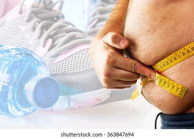 big man measuring his belly with a measuring tape and fitness background