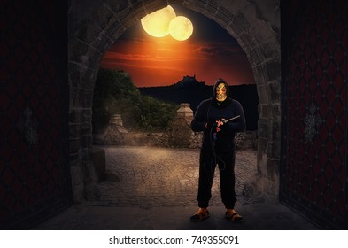 Big masked psycho wearing black hoodie holds a electric drill. Awful man might be waiting for someone in dark stone alley on two yellow moons background