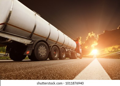 Big metal fuel tanker truck shipping fuel against dark sky with sunset