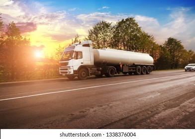 Big metal fuel tanker truck shipping fuel on the countryside road with trees against night sky with sunset