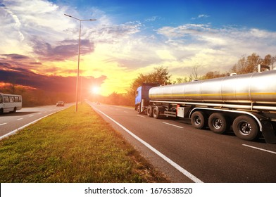 Big metal fuel tanker truck shipping fuel with other cars on the countryside road with trees against a night sky with a sunset