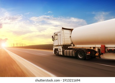 A big metal fuel tanker truck shipping fuel on the countryside road in motion against a blue sky with a sunset