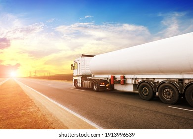 Big metal fuel tanker truck shipping fuel on the countryside road against a night sky with a sunset