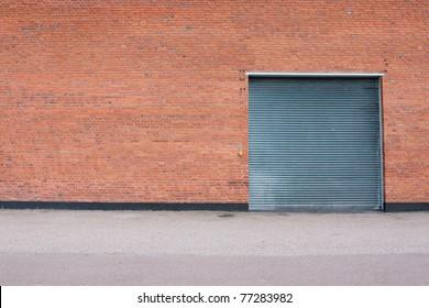 Big metal garage door on big brick wall.