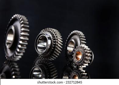 Big metal gears on glossy black background