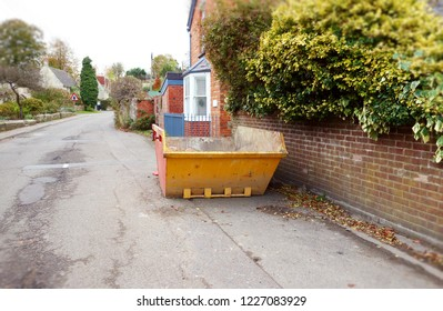 Big metal rubbish skip on side of road. Selective focus on the skip, some blurry surrounding background of road, wall, garden bush, houses. Space to add text on road surface. Renovate building concept