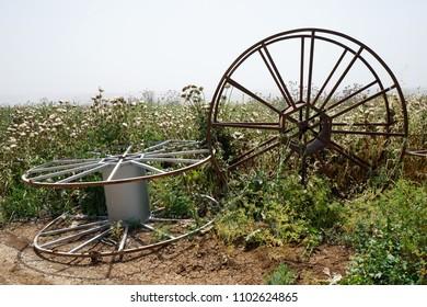 Big metal spools on the farm field