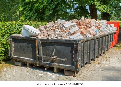 Big metal waste container filled with stones, toilet and other rubble