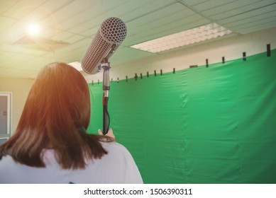 Big micro for movie maker hold by asian woman with green backdrop in background,back state production.