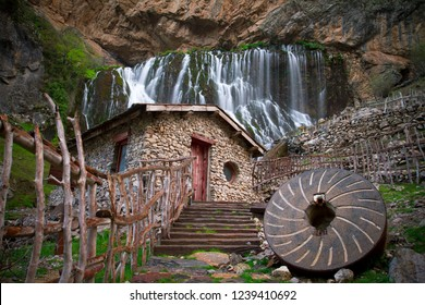 Big millstone, rock grinder in front of rocky farm house and waterfall. waterfall  make millstone move. Traditional water old wheel grain mill for grinding wheat in Kayseri, Kapuzbaşı, Turkey