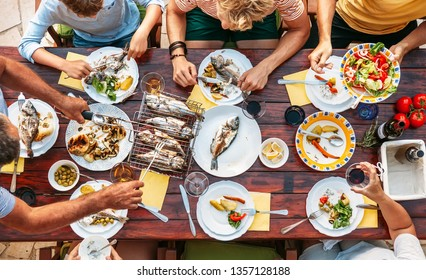 Big miltigeneration family dinner in process. Top view vertical image on table with food and hands