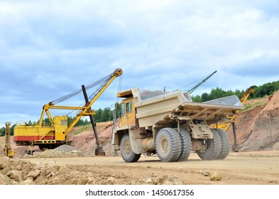 Big mining truck amid huge excavators in an open-pit quarry. Loading and transportation of stone ore in a limestone quarry. The photo was taken in the dolomite quarry in Vitebsk, Ruba village, Belarus