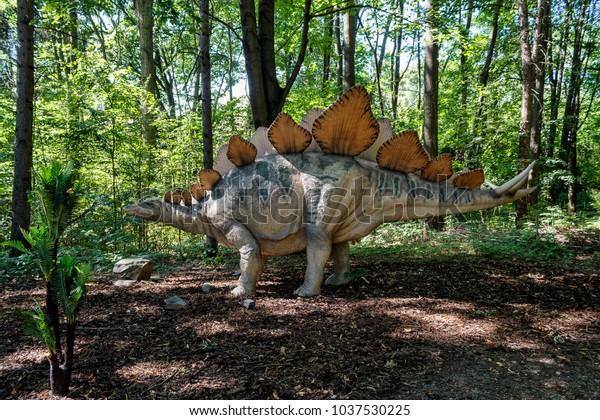 Big model of prehistoric dinosaur stegosaurus in nature. Realistic scenery.
