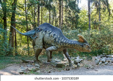 Big model of prehistoric dinosaur Troodon attack parasaurolophus. Realistic scenery.