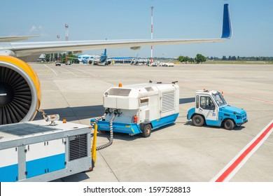 Big modern commercial plane parked on airport runway and connected to ground supply power unit. Aircraft maintenance service and check-up before flight. Airport handling industry