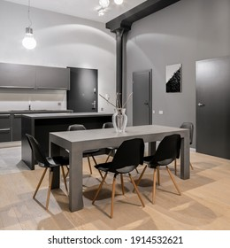 Big, modern and gray dining table with six black chairs in open kitchen in new loft apartment with dark doors
