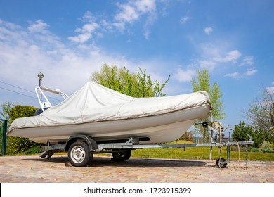 Big modern inflatable motorboat ship covered with grey or white protection tarp standing on steel semi trailer at home backyard on bright sunny day with blue sky on background. Boat vessel storage
