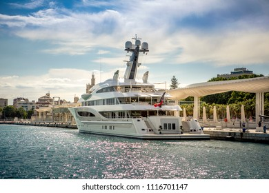 Big modern luxury yacht docked at port of Malaga, Spain, with a beautiful sunset light and the city in the background.