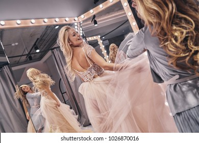 Big moment is coming.  Reflection of young woman adjusting a wedding dress on attractive bride while standing in the fitting room