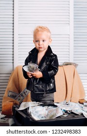 Big money. Little entrepreneur work in office. Small child do business accounting in startup company. Boy child with money case. Little boy count money in cash. Startup business costs.