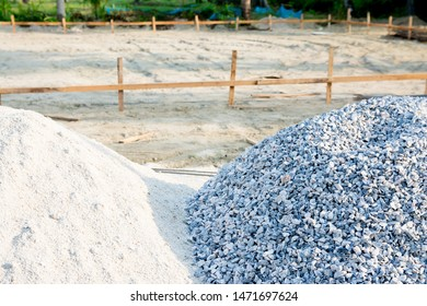 The big mound of crushed blue stone gravel and sand with blurry of construction area background.These small stones are important components in the construction of buildings, houses, roads.