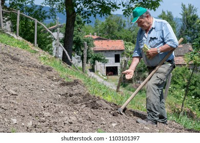 big mountain man works the land by sowing vegetables, in the background an old village