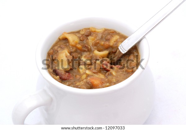 A big mug with delicious fresh German lentil soup and silver spoon isolated on white background