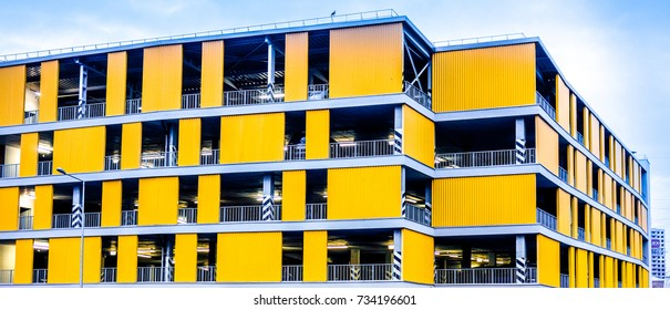 big multi store parking building for many cars in housing complex. Yellow home for many cars against blue sky and few cars near