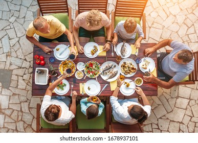 Big multigenerational family dinner in process. Top view image on table with food and hands. Food consumption and multigenerational family concept image.