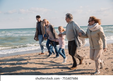 big multigenerational family holding hands and running together on beach at seaside