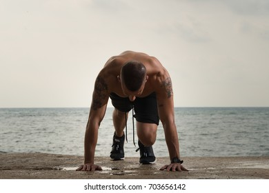 Big muscled guy doing push-ups on ground