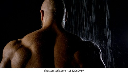 big muscular jock is standing in shower under water stream, back view in darkness