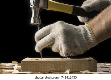 Big nail. A man in white gloves is hammering a big nail on the desk with black background. Shiny scrached hammer.
