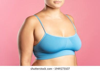 Big natural breasts in blue bra close-up on pink background, studio shot