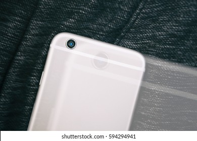 Big new silver smartphone on dark cloth.Modern smart phone model to stay always connected and take good pictures.Focus on camera lens.Double exposure